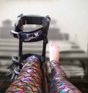 Foot amputee in rainbow fish scale leggings with iWALK2.0 hands free crutch