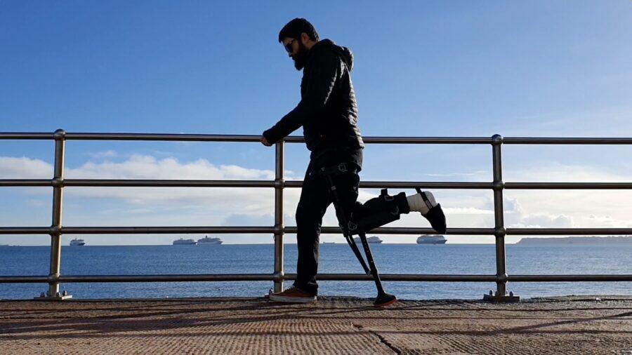 man with broken ankle walking along pier on iwalk crutch